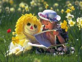 copil citinda o carte in iarba printre gladiole